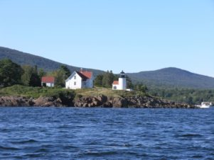 A view of Curtis Island Lighthouse from a sailboat in the bay